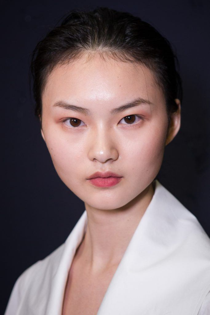 round faced asian model backstage at a fashion show