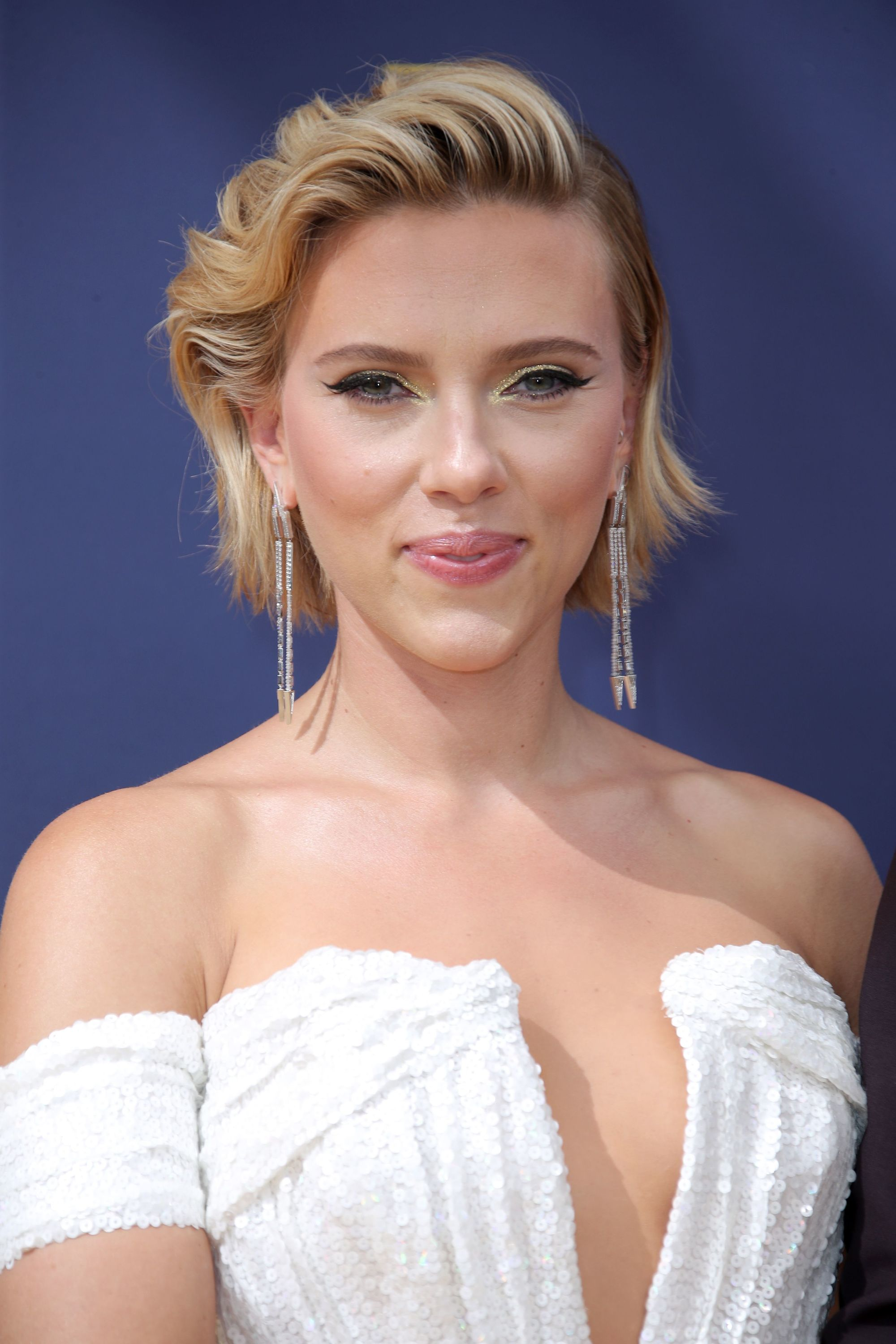 Emmy Awards 2018: Close up shot of Scarlett Johansson with golden blonde bob styled into undone, swept-back look, wearing drop earrings and a white dress on the red carpet