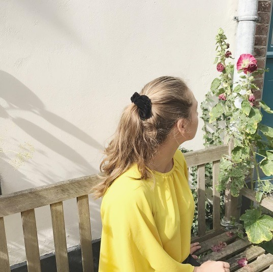 back view of a woman wearing a yellow top with her blonde hair in a scrunchie