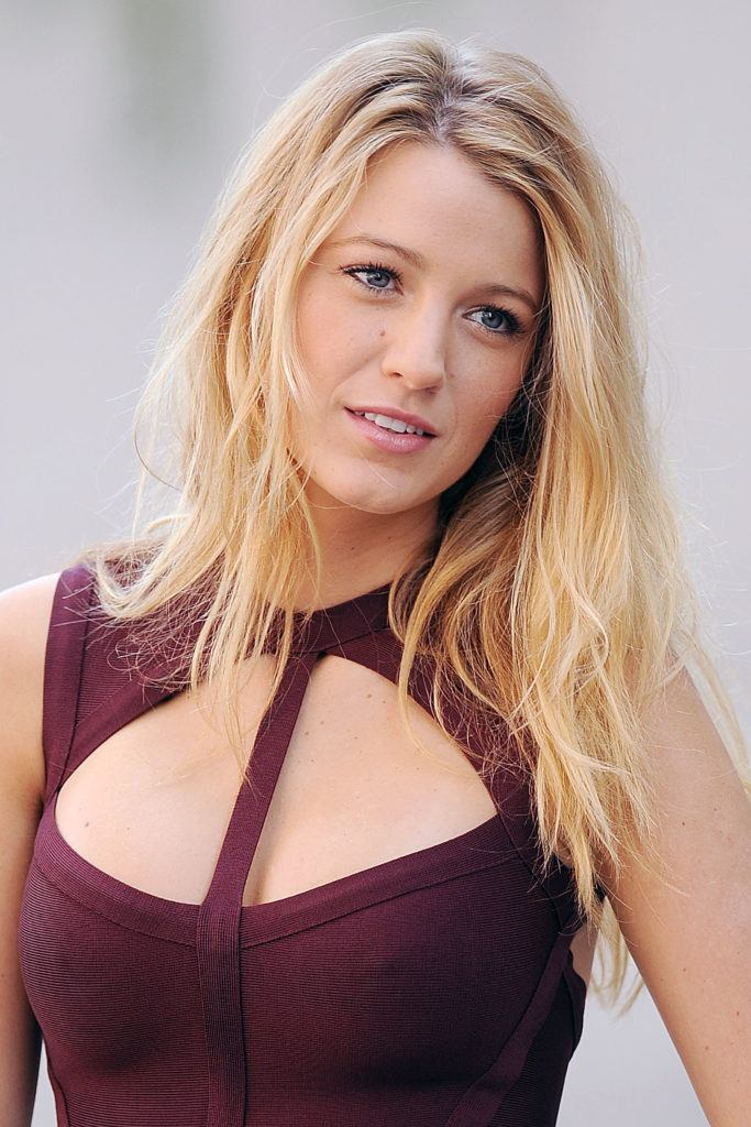 close up shot of blake lively with bedhead hairstyle, wearing a purple dress on the set of gossip girl