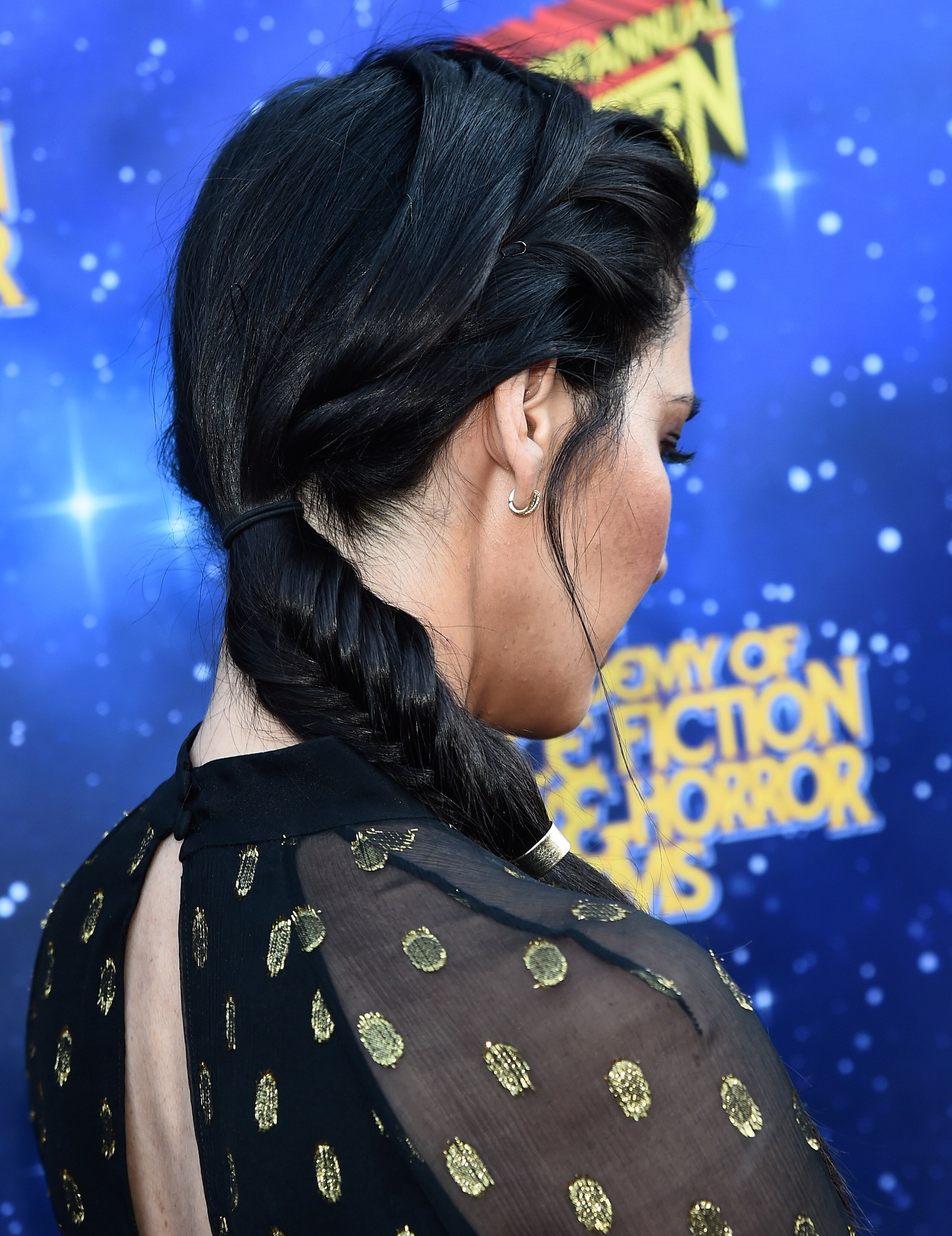 side shot of olivia munn with side fishtail braid hairstyle with a cuff on it on the red carpet