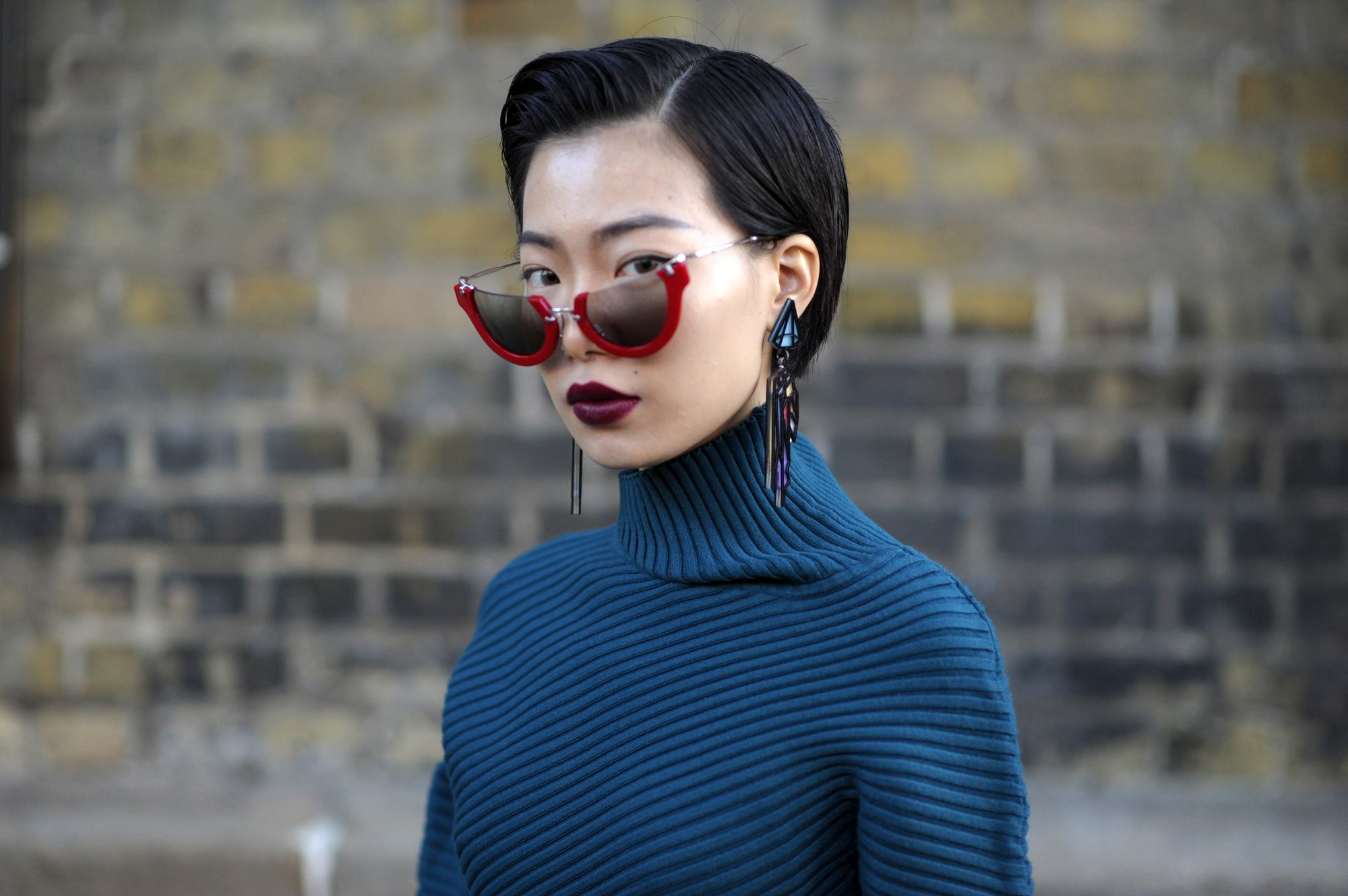 asian short hairstyles: close up shot of woman with short side-part pixie cut wearing blue jumper
