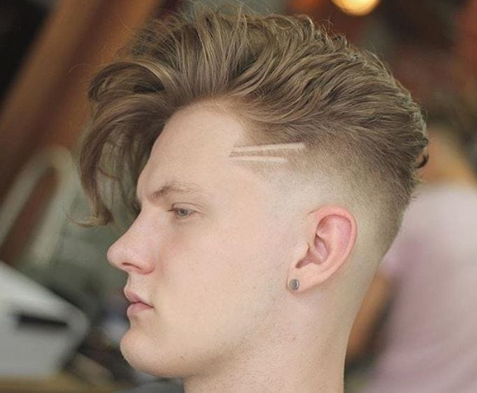 close up shot of man at a barbers with side part undercut with small pattern in it