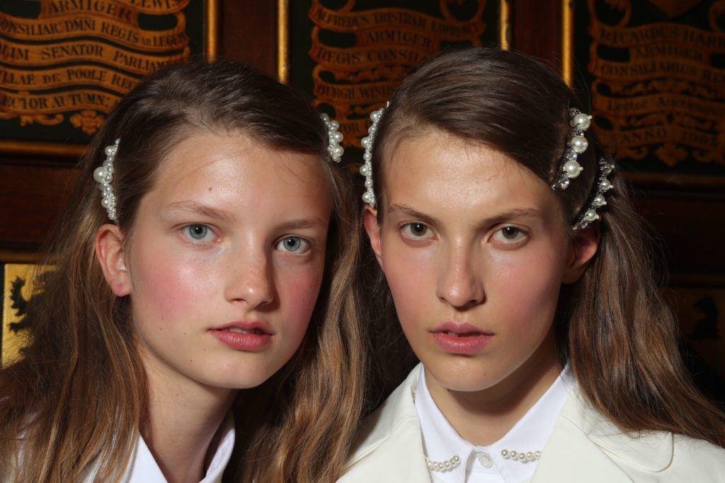 two brunette models backstage at the simone rocha show with pearl hair accessories