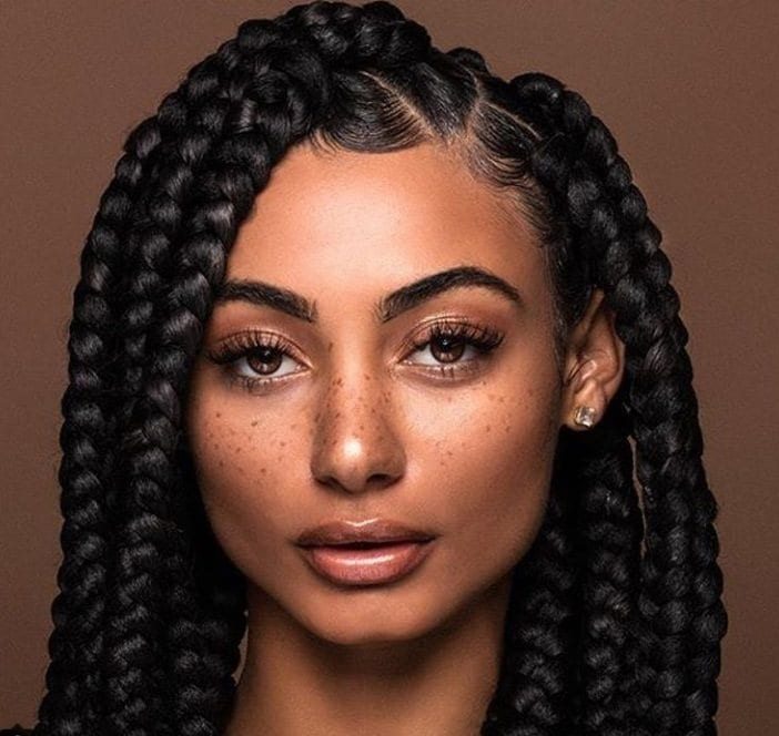 Dookie braids: Close up shot of a model with chocolate brown sleek big box braids.