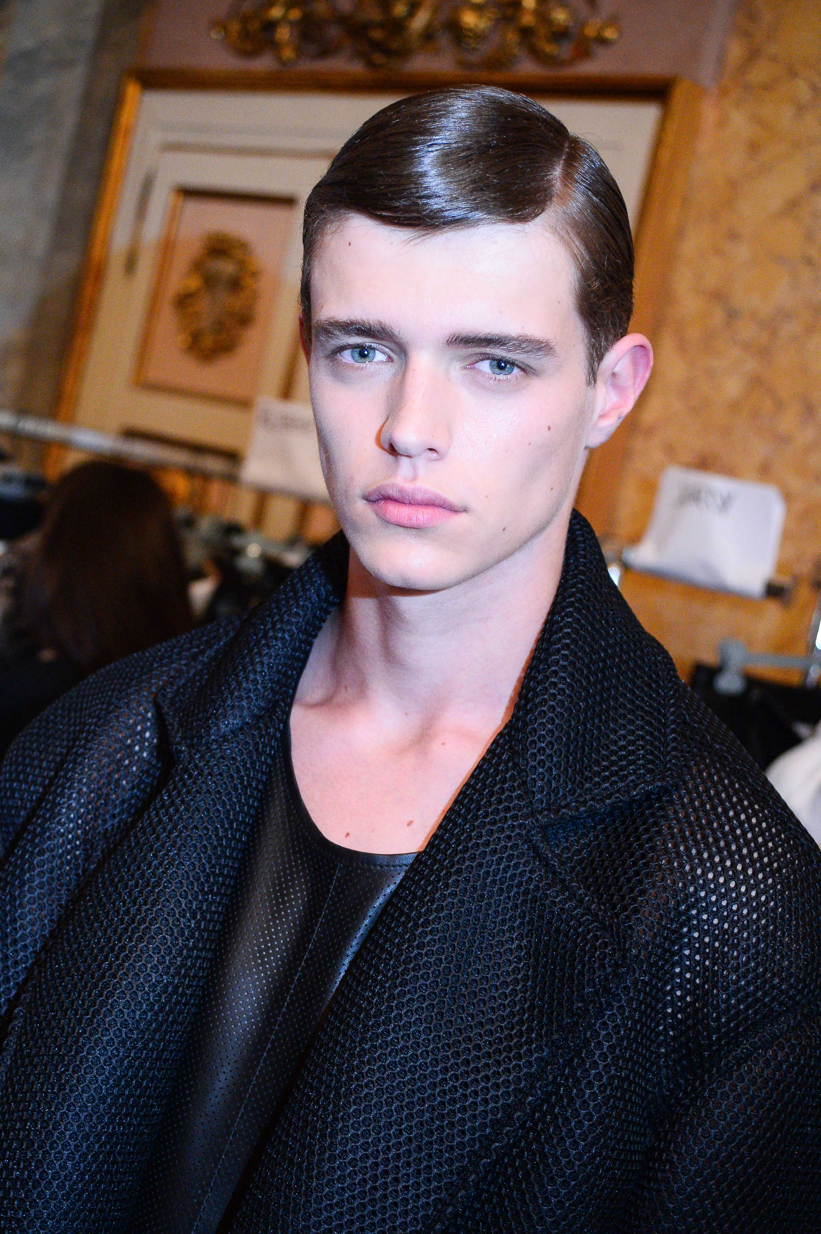 brunette male model backstage with slick comb over hair