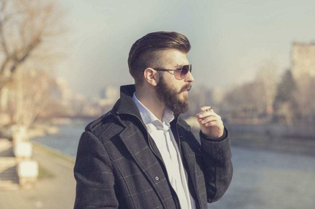 Slicked back undercut: Side profile of a brown haired man with a slicked back haircut with shaved sides and a beard