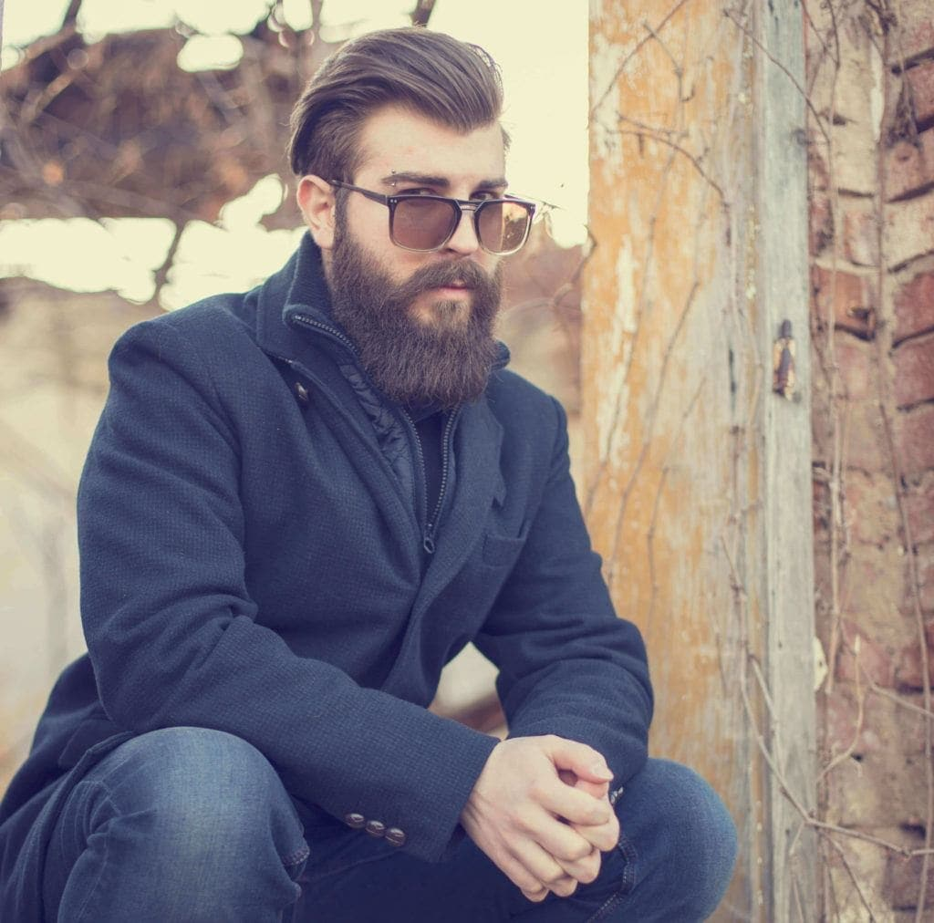 Slicked back undercut: Photo of a man with swept back brown hair with a subtle taper and a beard