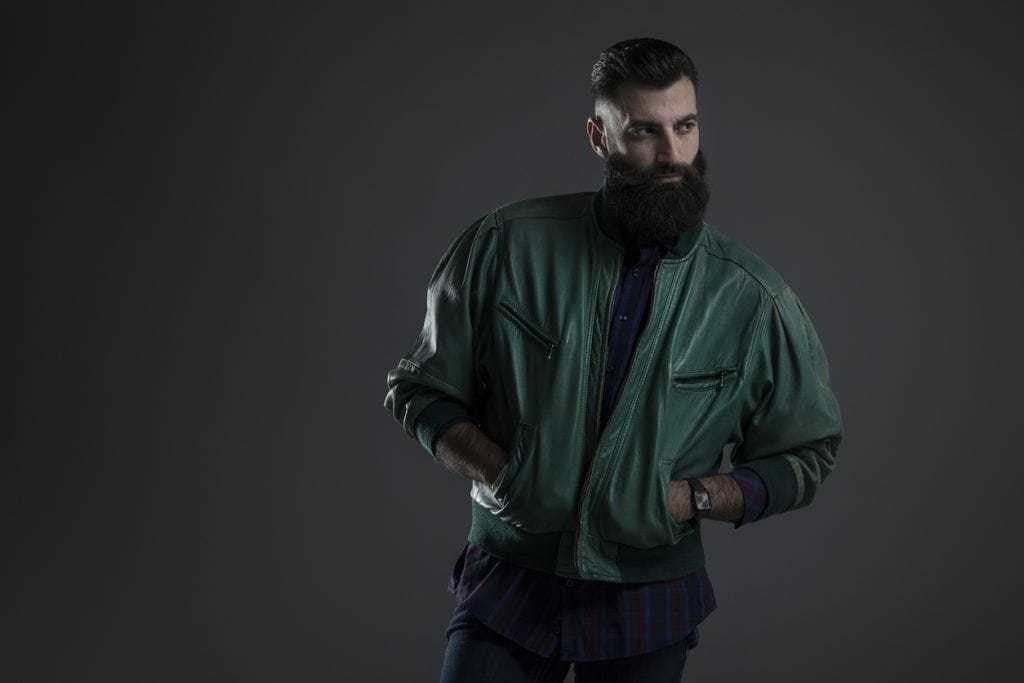 Slicked back undercut: Dark haired man with a slicked back undercut and shaved sides with a beard, wearing a green leather jacket