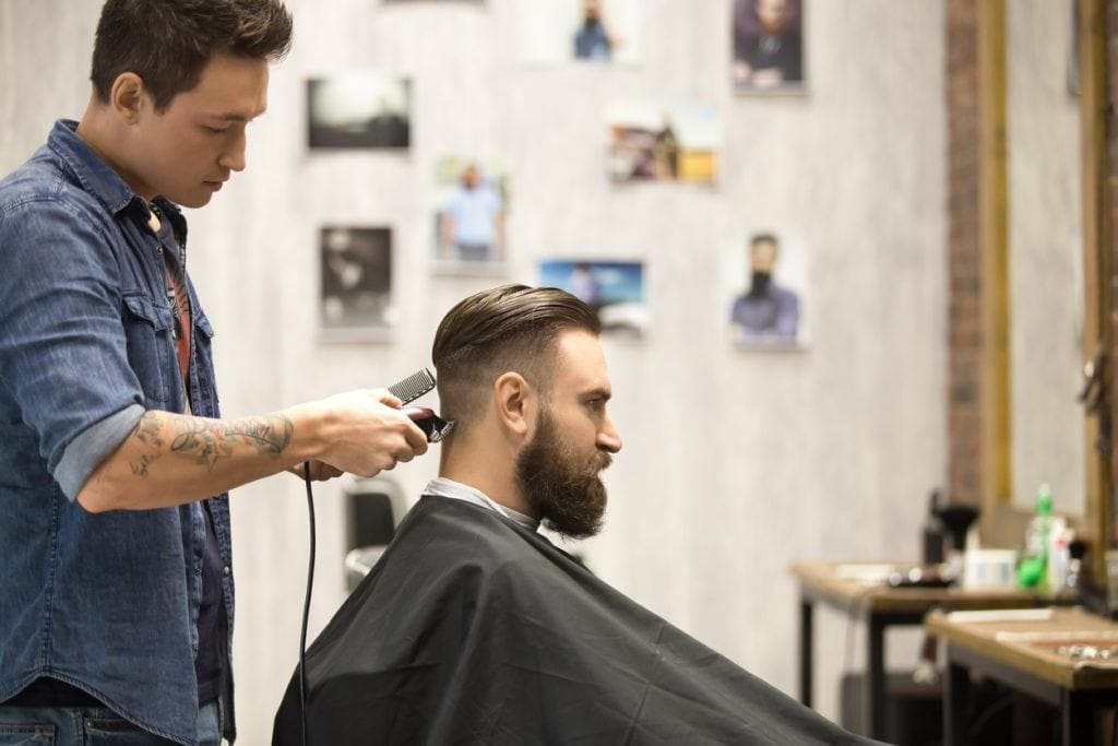 Slicked back undercut: Photo of a man in a barber shop with a slicked back undercut having clippers used on him by a barber