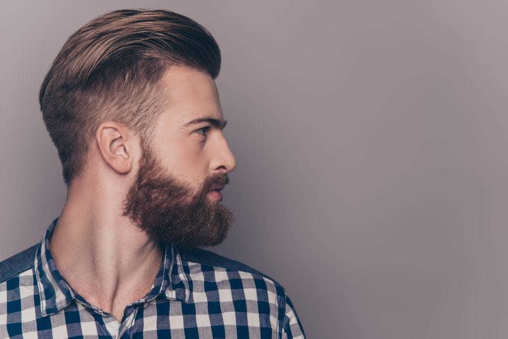 Slicked back undercut: Side profile shot of a man with brown hair with a medium length undercut and long, slicked back top layers, wearing a checkered shirt