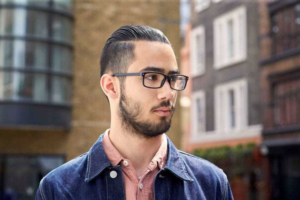 Slicked back undercut: Dark haired man with a gelled, slicked back style with an undercut, with facial hair, wearing glasses and a pink shirt and denim jacket
