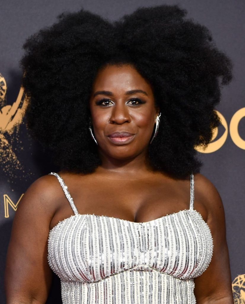 close up shot of uzo aduba with big afro hairstyle wearing white dress on the 2017 emmy awards