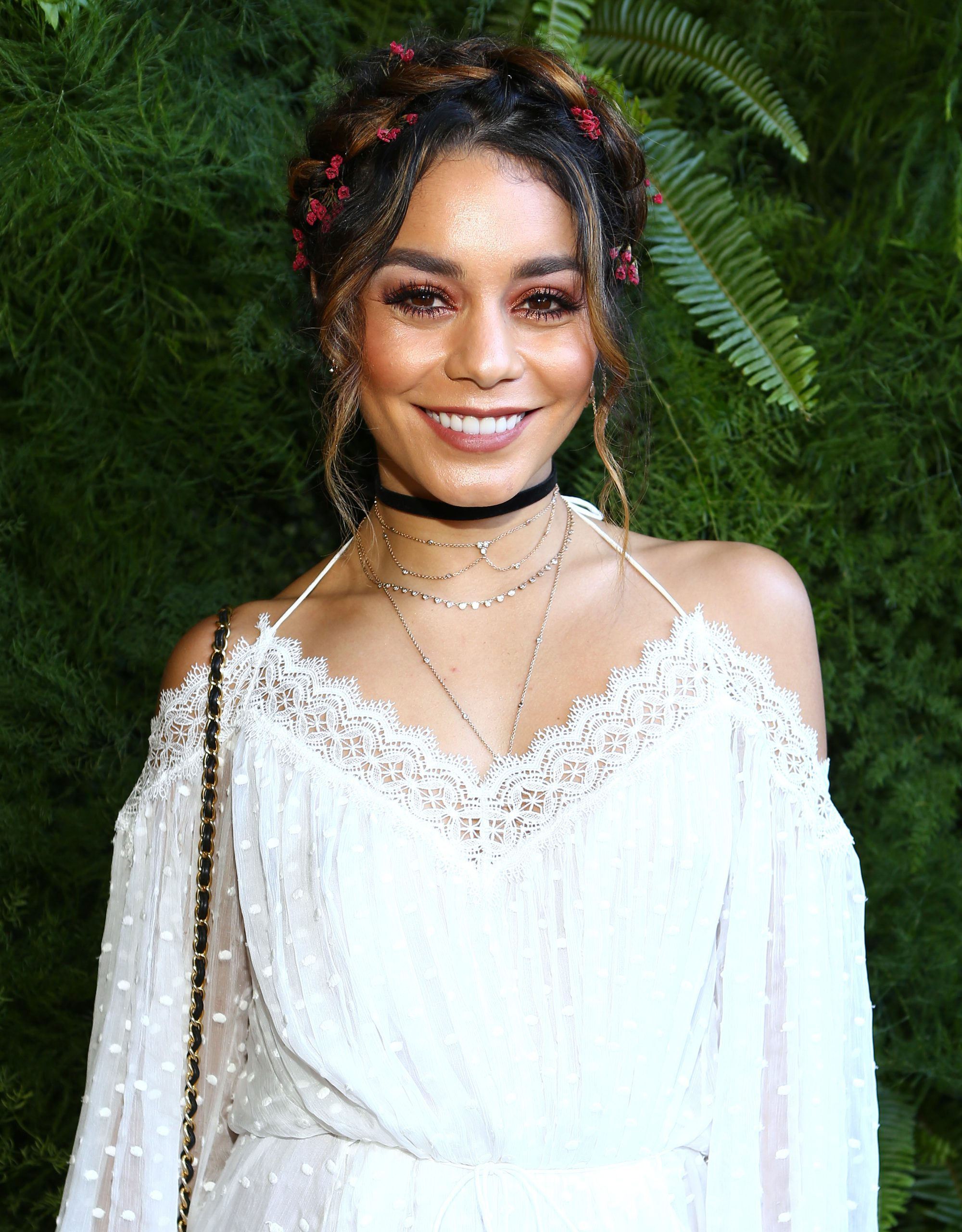 party braids inspiration: shot of vanessa hudgens with floral milkmaid braid wearing white and smiling