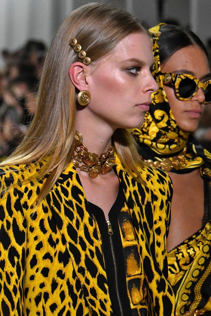 shot of model on the versace runway with golden hair slide wearing yellow and black jacket
