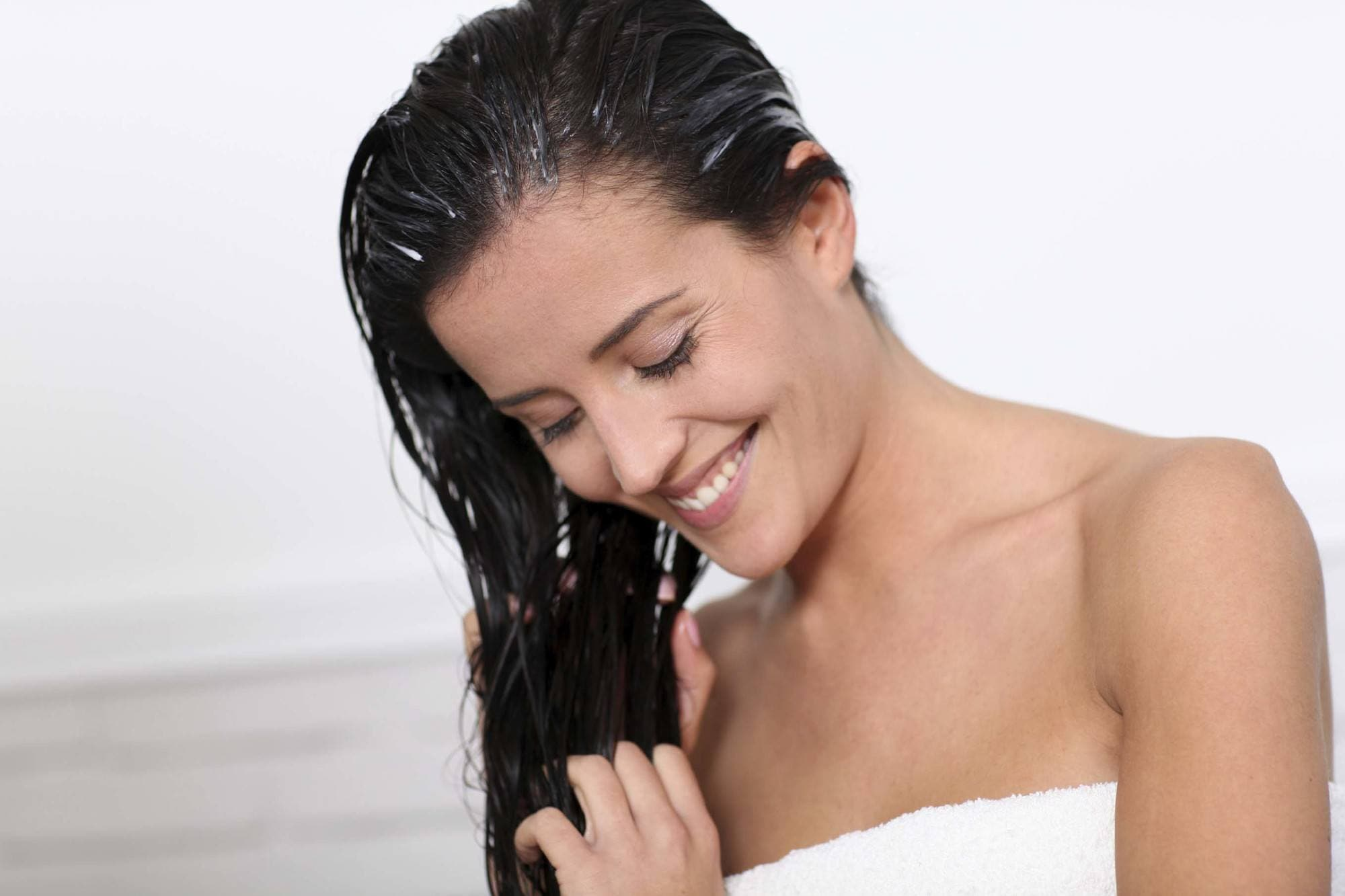 model with brown hair applying conditioning product to lengths of hair