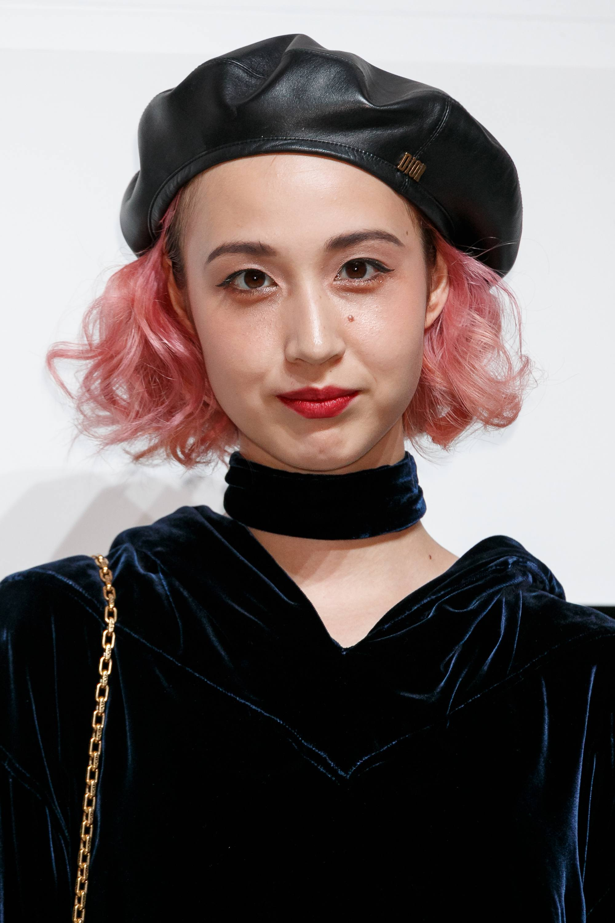 close up shpt of woman with short pink asian hairstyle wearing a black beret and velvet jumper