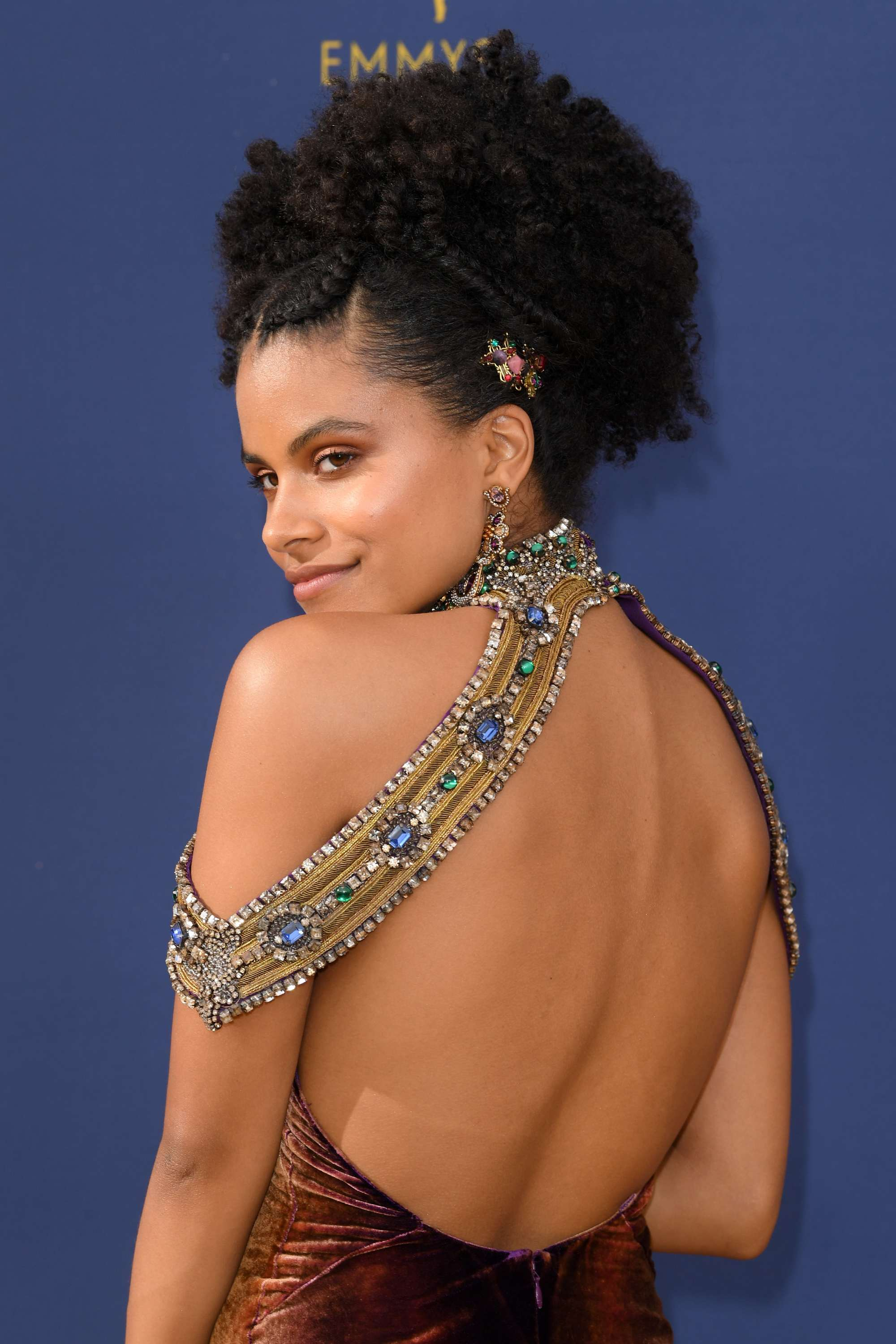 Emmy Awards 2018: Close up shot of Zazie Beetz with a glamorous high afro bun with braid detailing and an ornamental hair clip, wearing a matching bejewelled dress on the red carpet