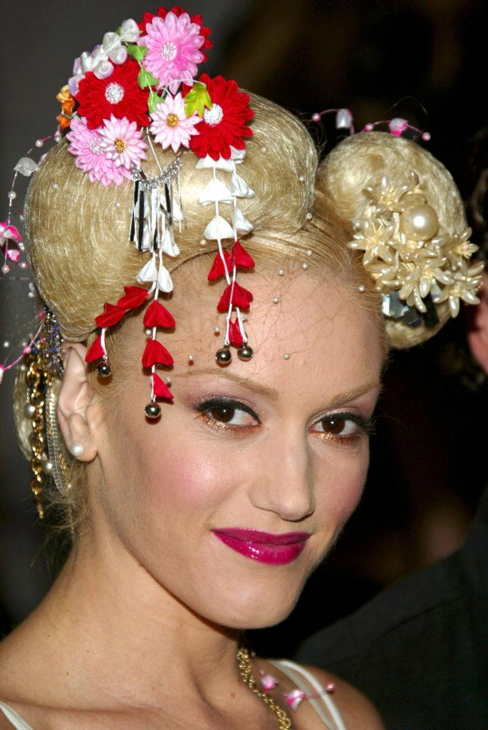 Gwen Stefani platinum blonde hair in space buns with red accessories