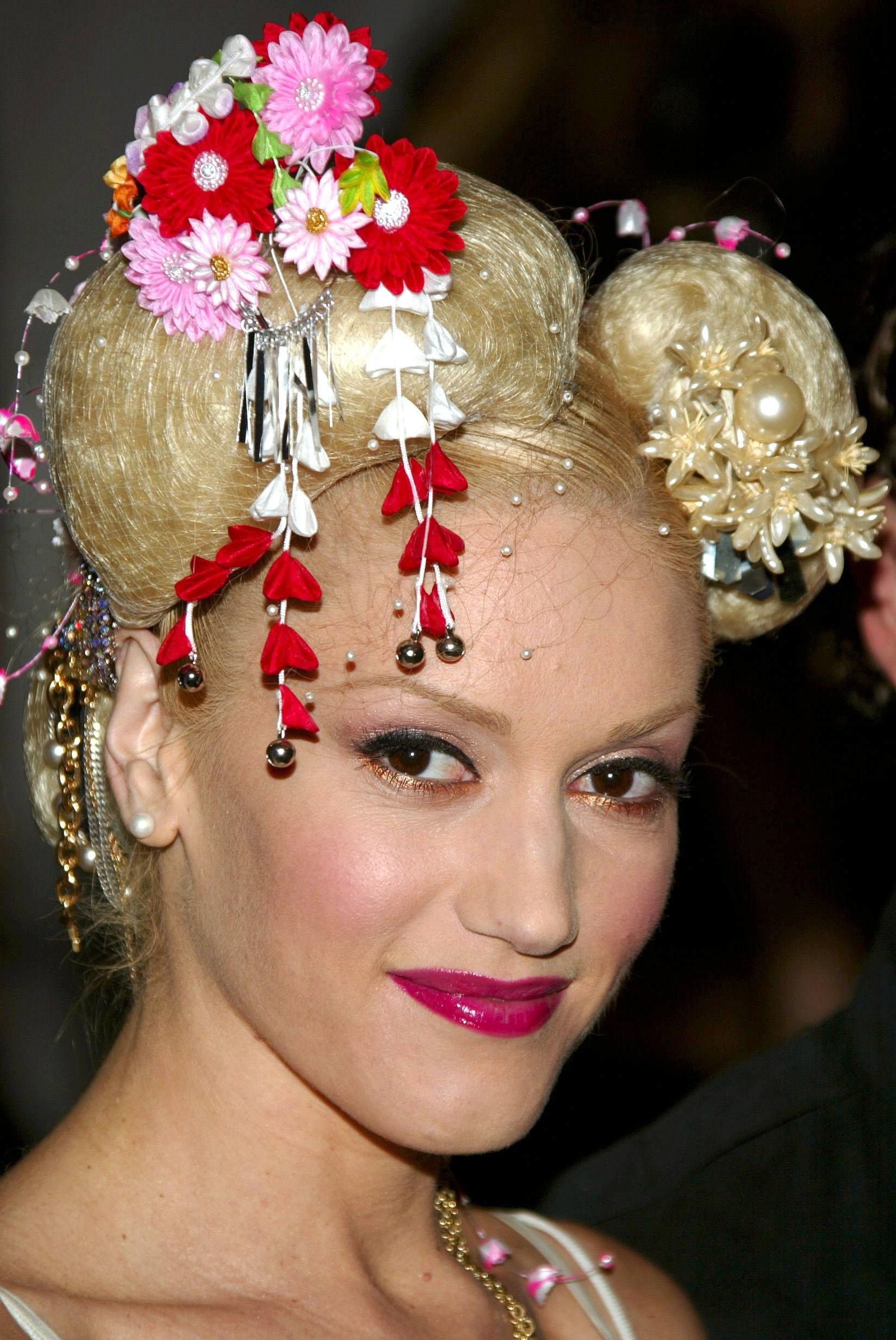 Mane moments gwen stefanis hair highlights from then to now gwen stefani platinum blonde hair in space buns with red accessories sciox Images