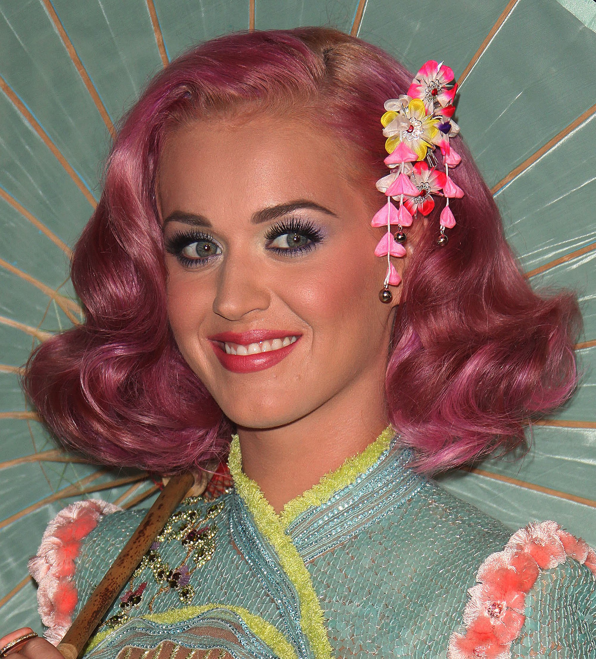 Katry Perry side parting shoulder length pink curly hair with floral accessory