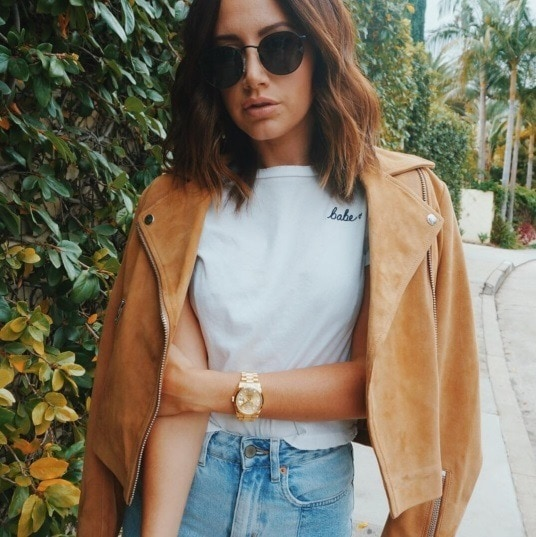 Fall hair colours: Actress Ashley Tisdale with shoulder length medium brown hair wearing large circle sunglasses wearing a tan suede jacket, t-shirt and jeans.