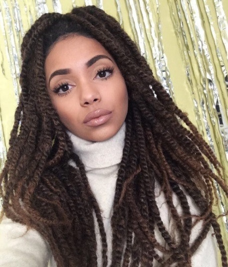 Woman in a roll neck cream jumper with long brunette box braid twists