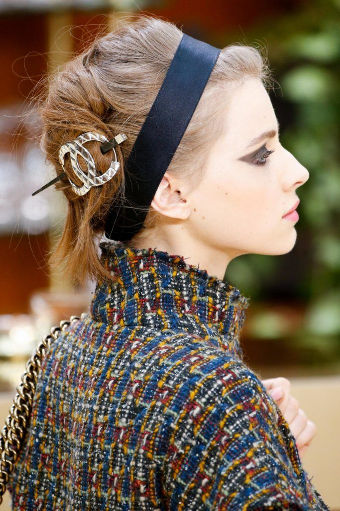 vintage updo hairstyles: close up shot of model on the chanel runway with vintage updo hairstyle with hair accessory, wearing chanel clothing
