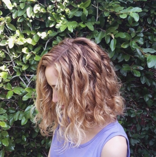 side profile picture of a woman with bob length copper balayage curly hair
