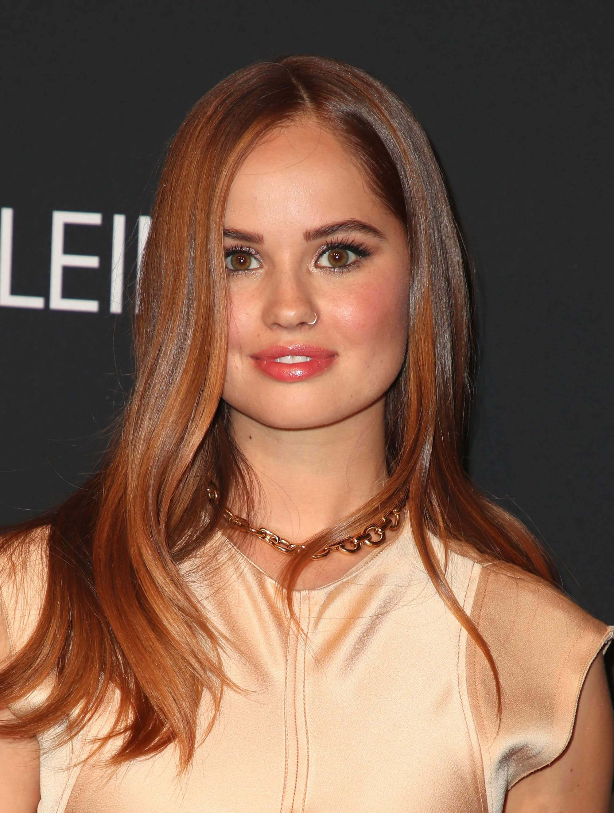 Fall hair colours: Debby Ryan with long straight brown auburn hair with a soft wave wearing a ivory silk dress.