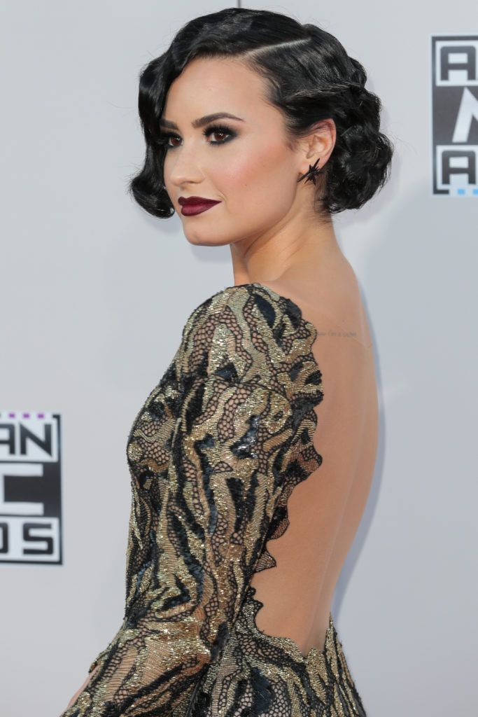 1920s hairstyles: demi lovato at american music awards with finger wave dark brown bob wearing backless dress