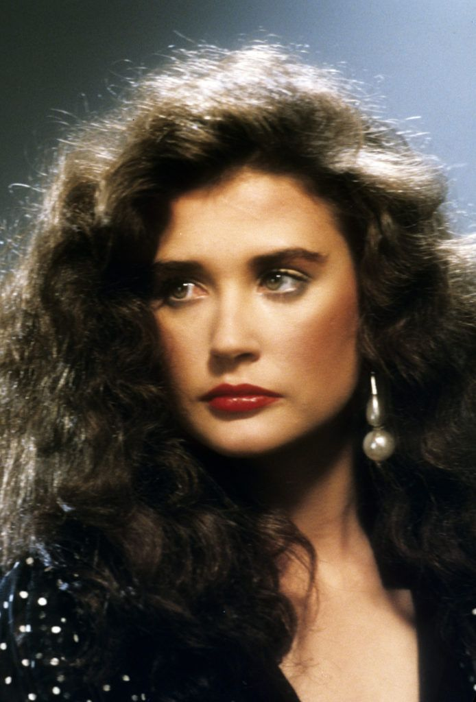 80s hairstyles: Young Demi Moore with brown curly wavy big '80s hair wearing a drop earring in close up image