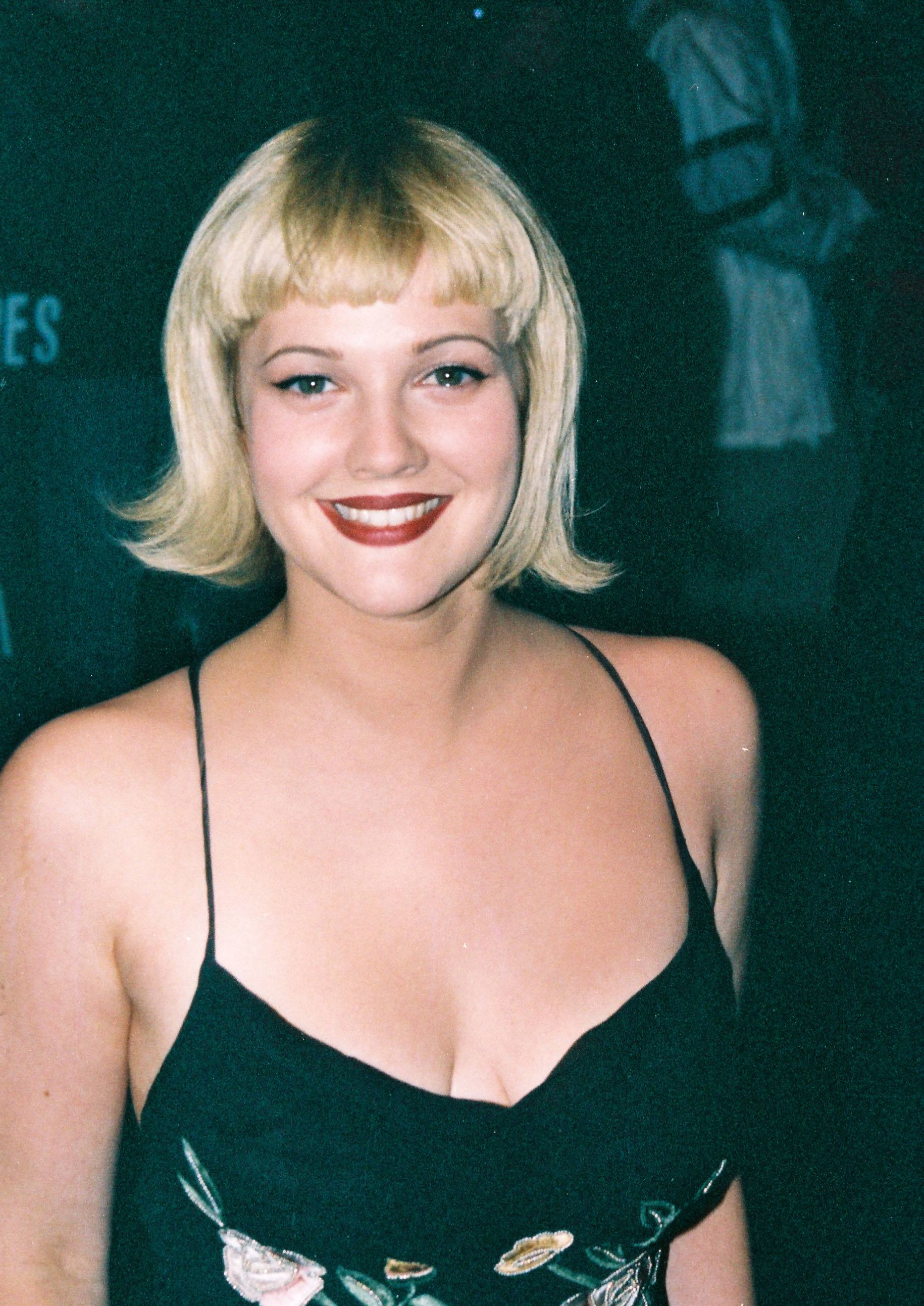 90s hairstyles: Drew Barrymore blonde bob with distinctive flipped out ends with micro fringe. Drew is wearing a black dress