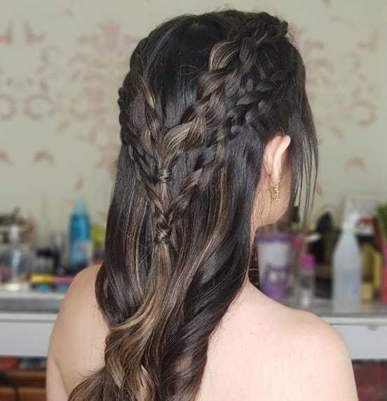 Medieval hairstyles: Back view of a woman with brown curled hair in a half-up braided style