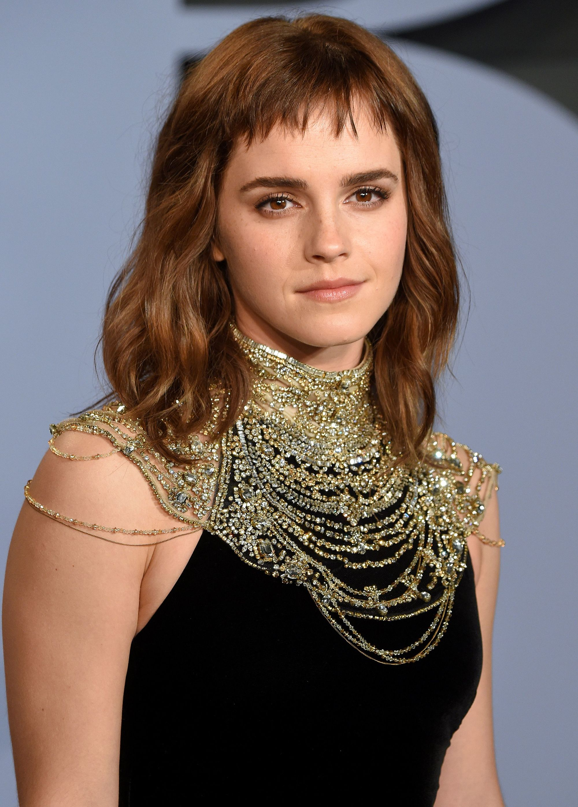 Short bangs: Emma Watson with shoulder length wavy brown hair with short micro fringe wearing a black dress with chain neckline.
