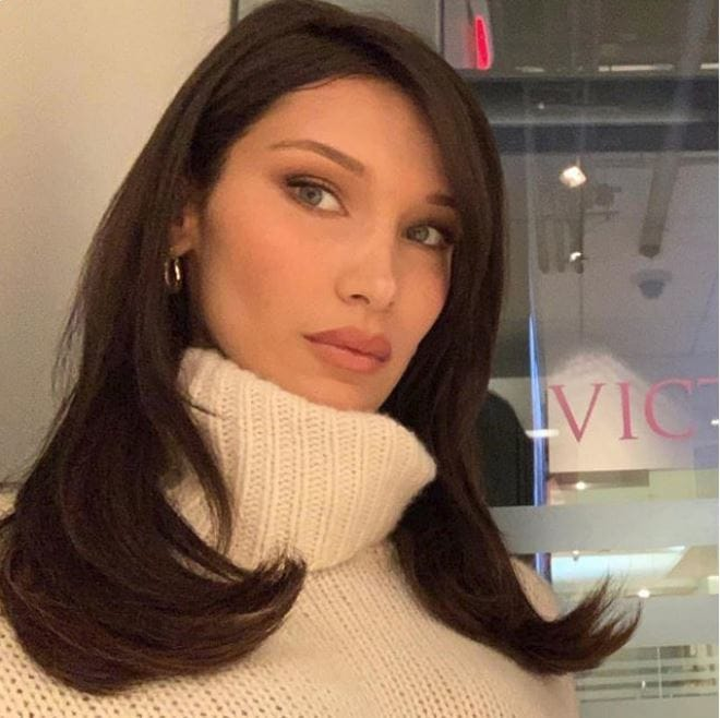 Fall hair colours: Bella Hadid with chocolate brown medium length hair wearing a high neck cream knit jumper.