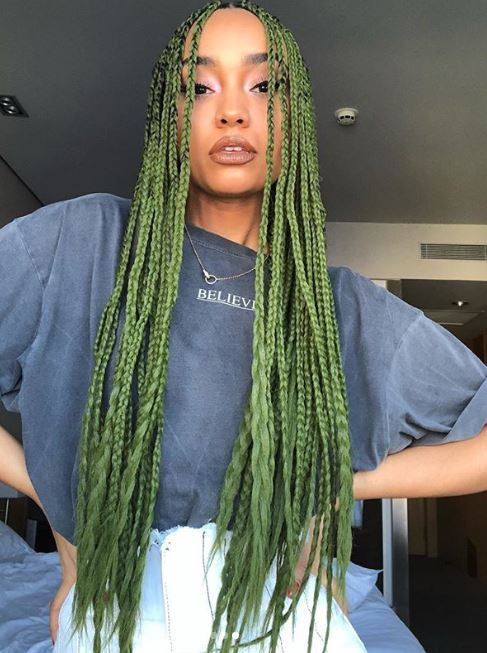 Fall hair colours: Leigh-Anne Pinnock with vivid green long box braids wearing a faded blue top and white bottoms.