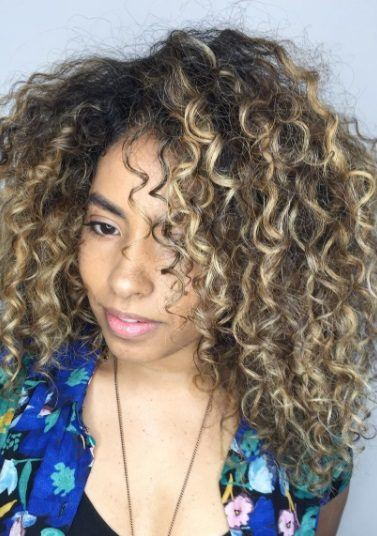 woman with brunette curly afro hair with blonde balayage