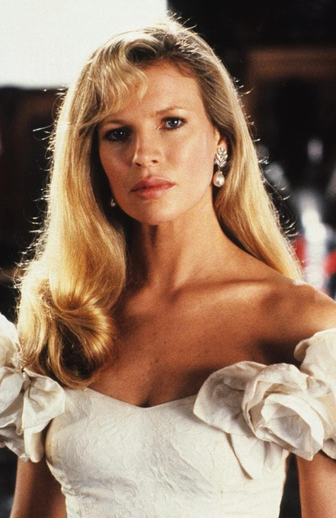 80s hairstyles: Kim Basinger long blonde hair in side parted '80s style with off the shoulder white dress