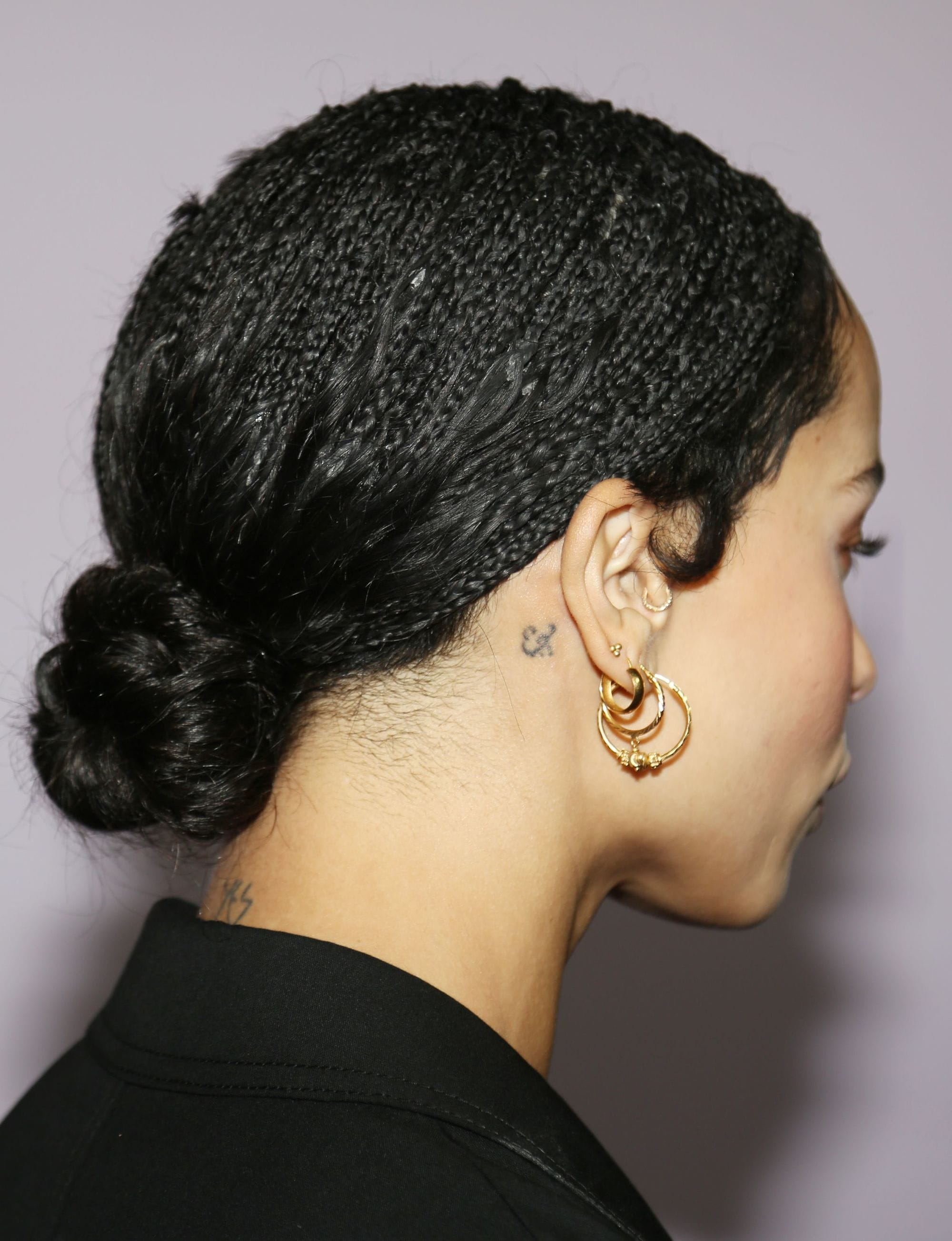 Loose box braids: Back shot of Zoe Kravitz with box braids with loose ends styled into a sleek, low bun.
