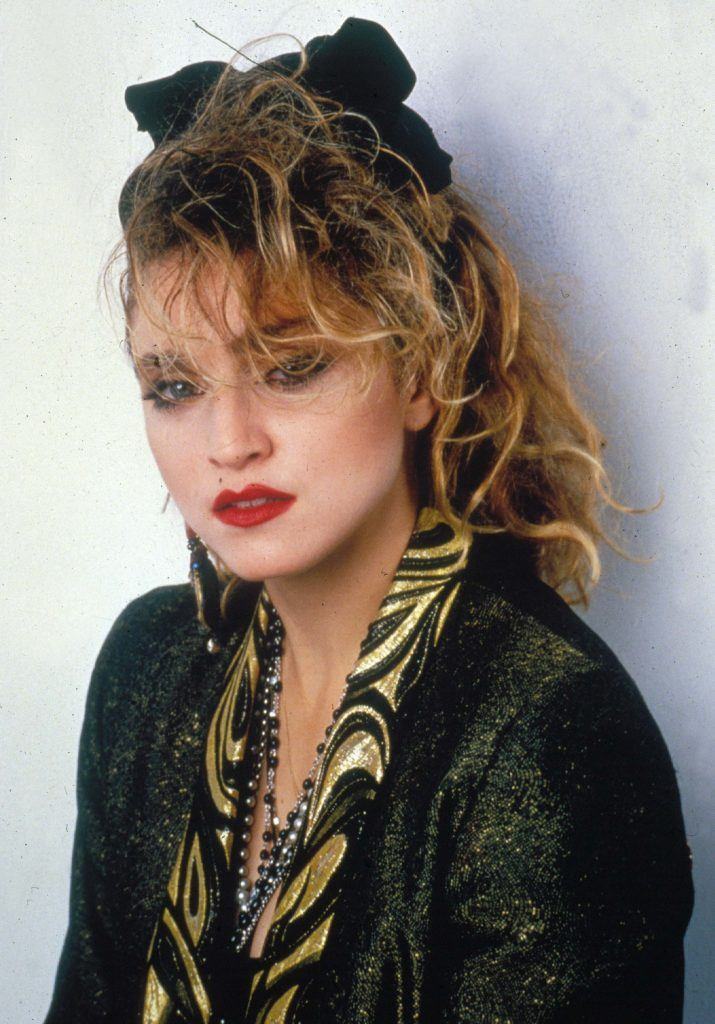 80s hairstyles: Madonna with '80s style curly updo with a black headband wearing a leather jacket and bold make-uo