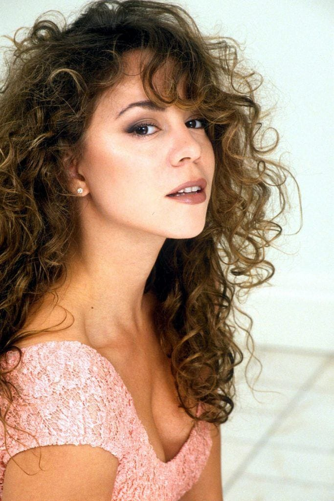 90s hairstyles: Mariah Carey with naturally curly brown hair with side bangs wearing a pink dress