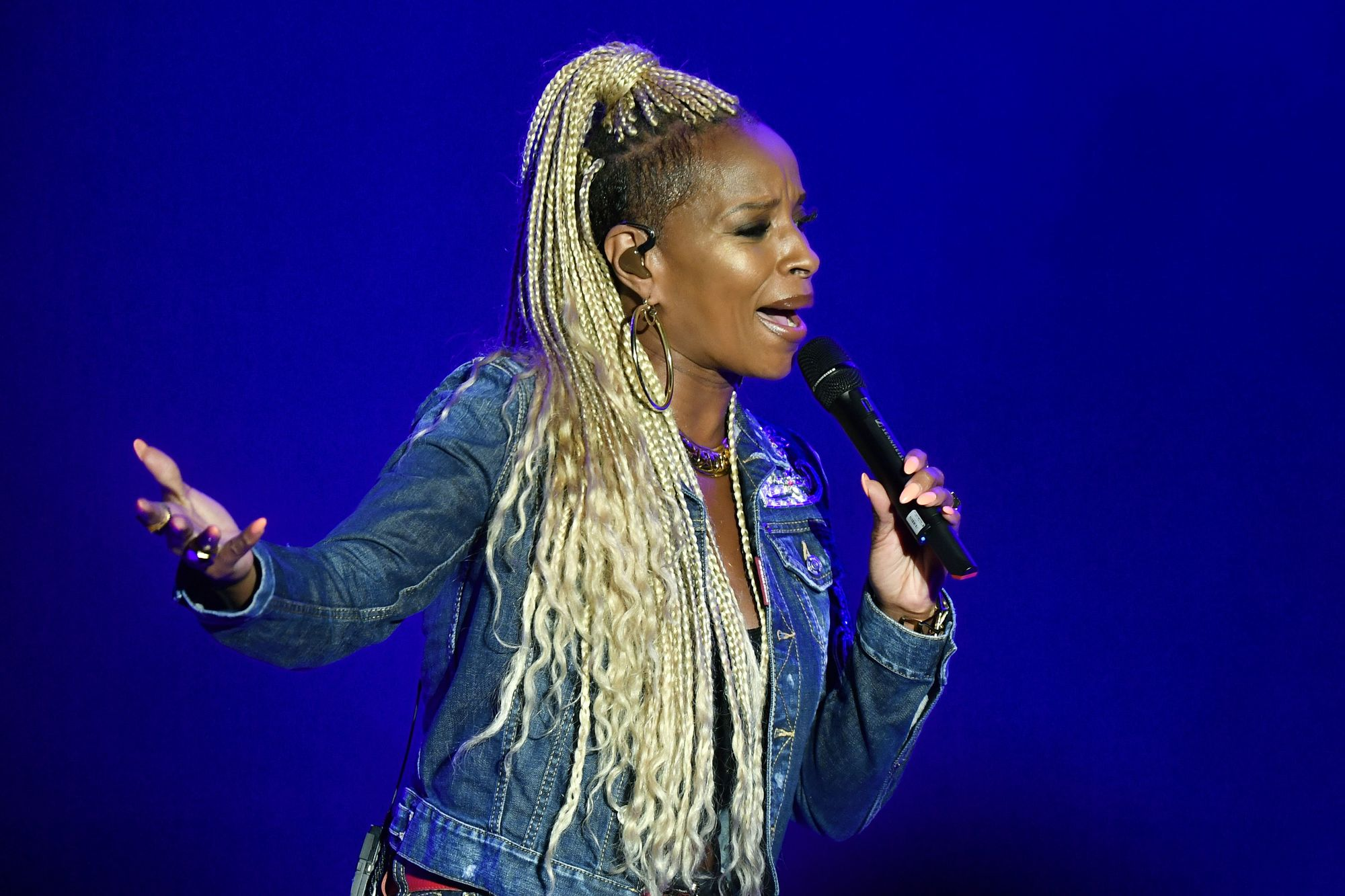 Loose box braids: Side shot of Mary J. Blige in concert with platinum blonde long box braids and an undercut, wearing denim and singing on stage.