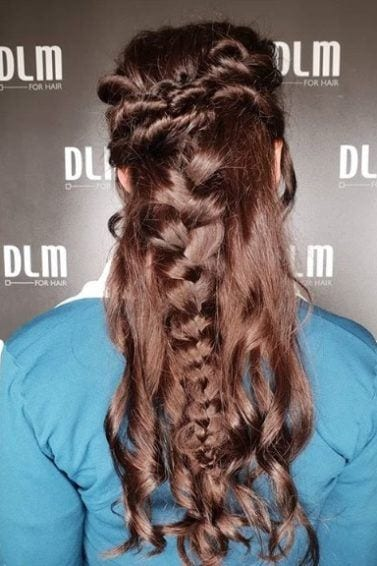 Medieval hairstyles: Back view of a woman with glossy brown long curled hair in medieval style half-up Dutch braids