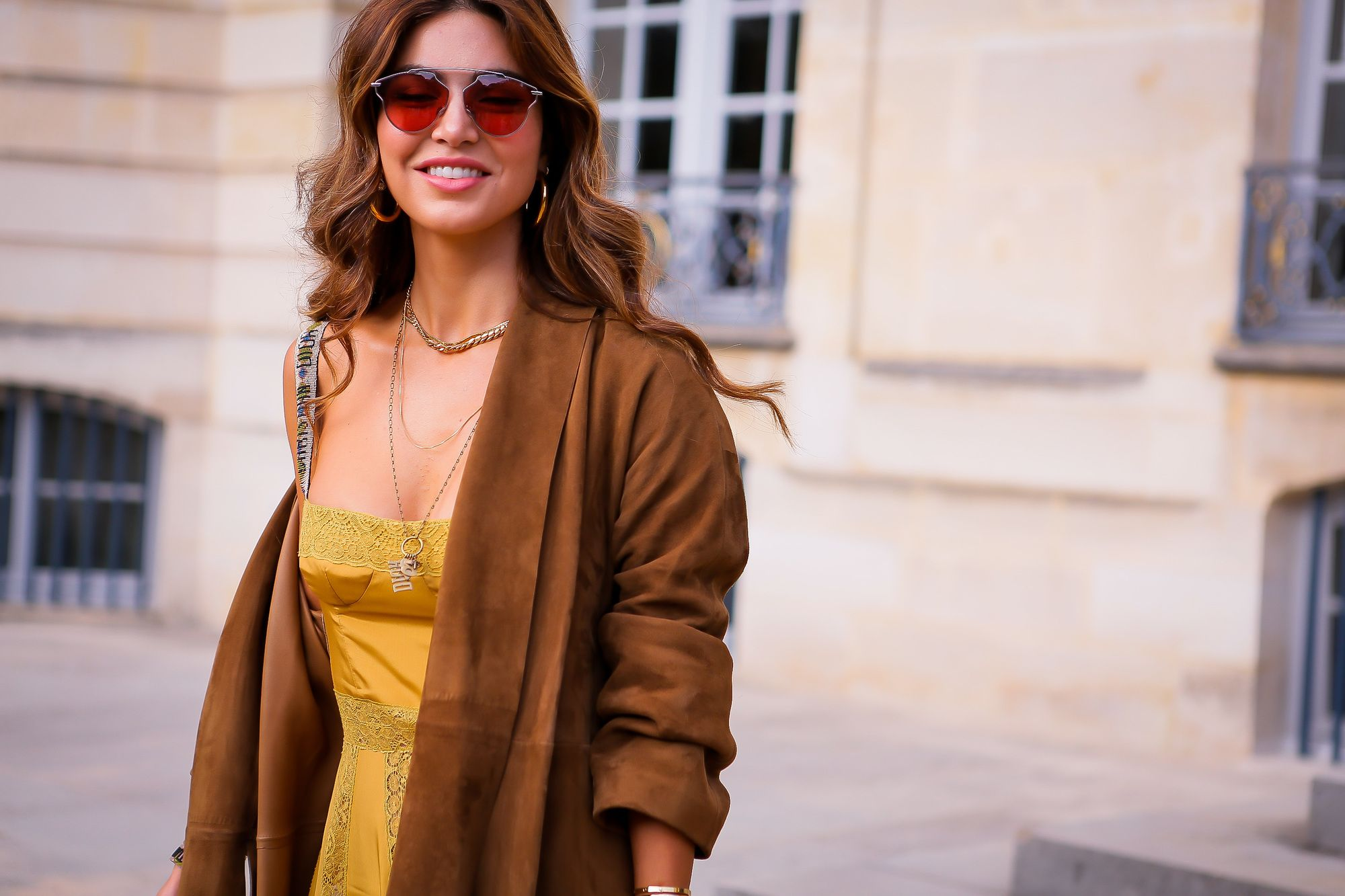 street style paris fashion week shot of a woman with curly cinammon brown hair