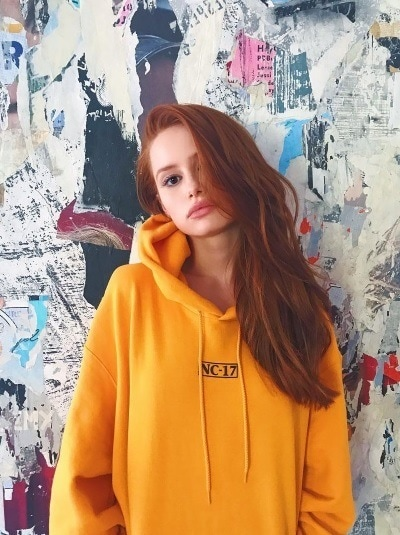 Fall hair colours: Riverdale actress Madelaine Petsch with long fiery red tousled hair wearing a large oversized yellow hoodie standing against a pattern wall.