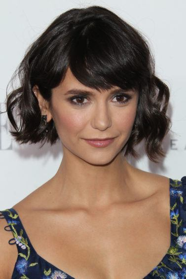Nina Dobrev dark brown hair in side part bob with full sweeping fringe