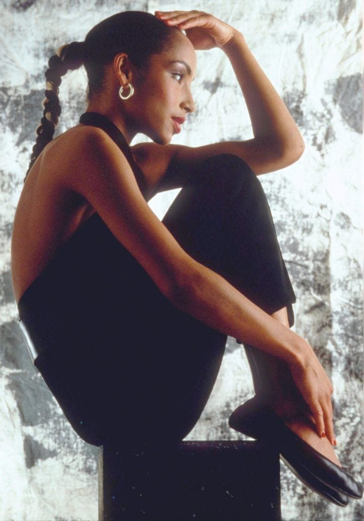 80s hairstyles: Side profile of Sade with long dark brown hair styled in a smooth ponytail braid