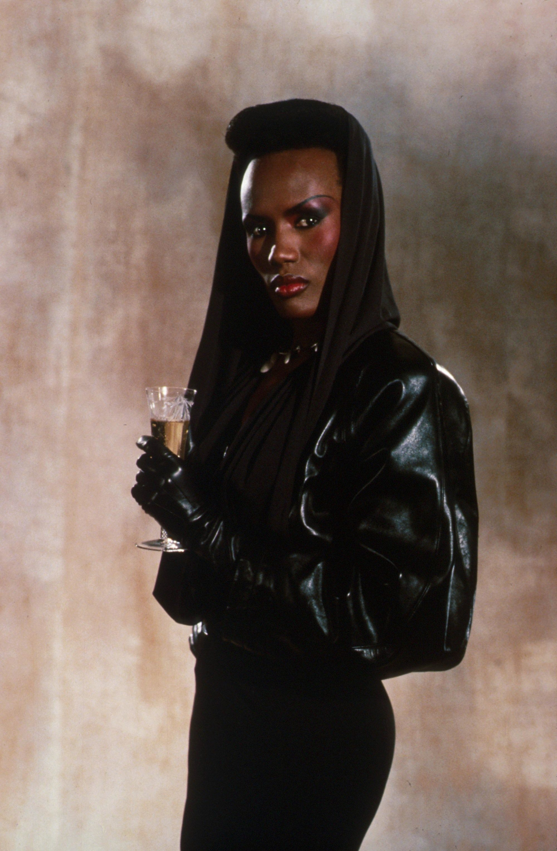 80s hair: Grace Jones high top afro natural hair wearing a black hood in '80s image