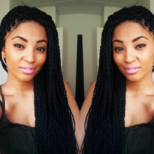 Double selfie of a woman with sideswept dark brown/black box twists